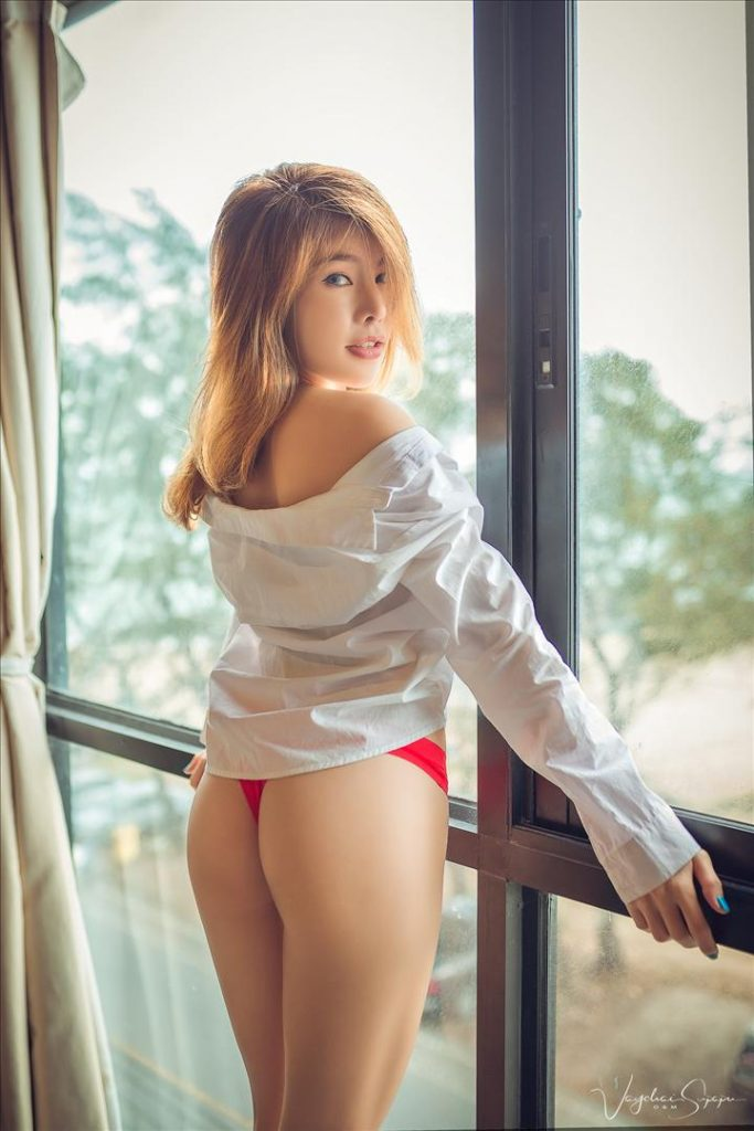 Vong Thammavong in red lingerie and white shirt against a window
