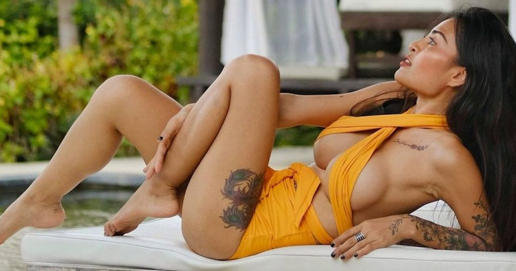 Thai model coco suay wearing an orange swimsuit by the pool in Pattaya