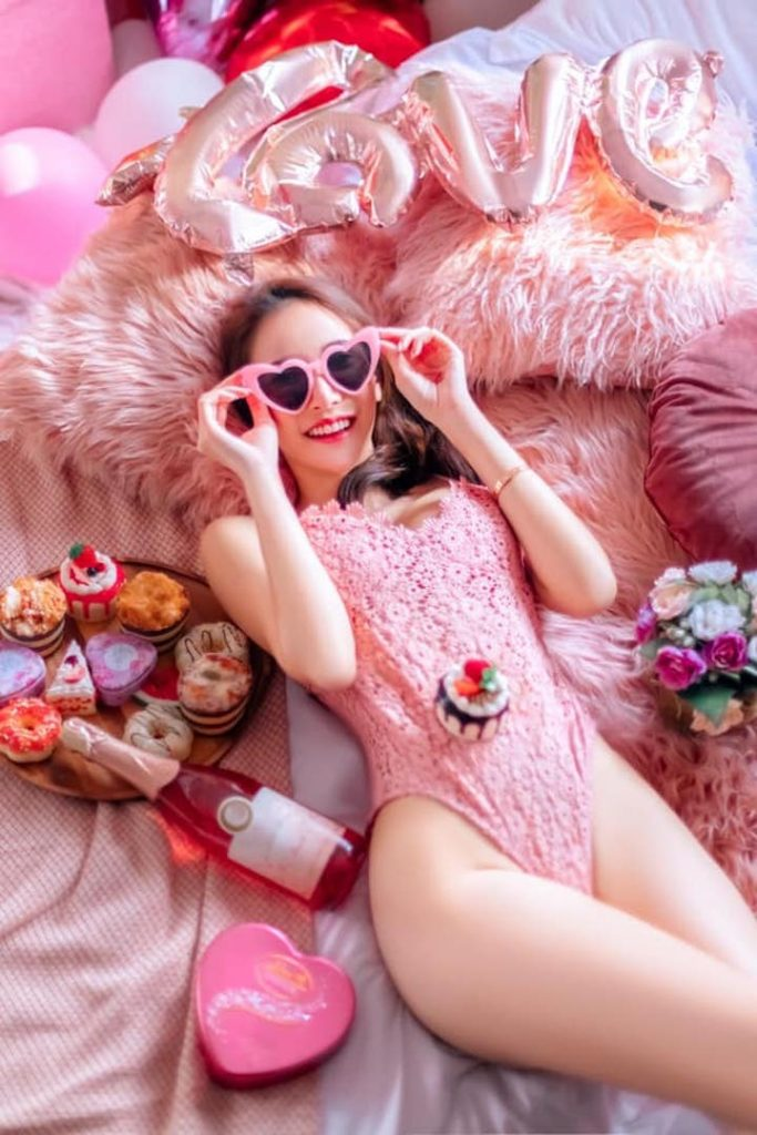 Metita Ritseeboon dressed in pink laying on a bed with sweet treats and balloons