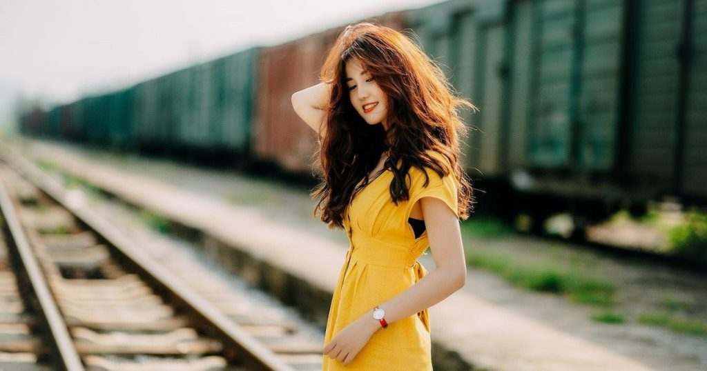Thai girl wearing a yellow dress on a rail track in Thailand